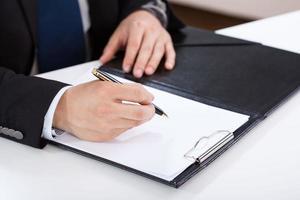 Hände des Geschäftsmannes, der auf Zwischenablage schreibt