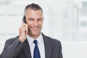 fröhlicher Geschäftsmann, der Kamera beim Telefonieren betrachtet foto