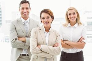 glückliche Geschäftsleute mit verschränkten Armen im Amt foto