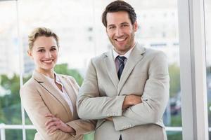 Geschäftsleute, die mit verschränkten Armen lächelnd an der Kamera aufwerfen foto