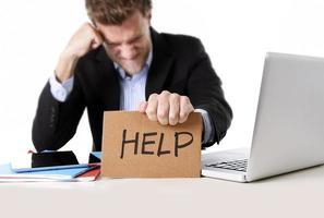 Geschäftsmann, der im Stress am Computer arbeitet, der Hilfekartonzeichen hält foto