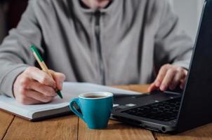 junger Mann, der Notizen vor Laptop schreibt foto