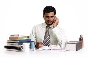 glücklicher indischer junger Geschäftsmann, der im Telefon spricht foto