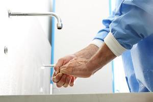 Der Arzt desinfiziert seine Hände