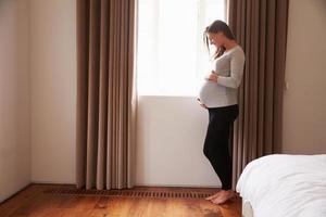 schwangere Frau, die durch Fenster im Schlafzimmer steht, das Bauch hält foto