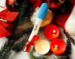 Schwangerschaftstest positives Ergebnis Frohe Weihnachten präsentieren rote Ribbo foto