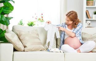 Schwangere werdende Mutter bereitet Kleidungsstücke für Neulinge vor foto