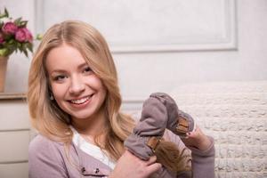 junge attraktive Frau, die Babyhandschuhe hält, Innenaufnahme foto