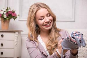 junge attraktive Frau, die Babymütze hält, Innenaufnahme foto