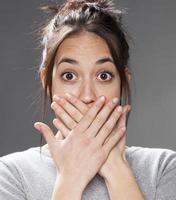 sprachloses multiethnisches Mädchen der 20er Jahre mit Händen auf dem Mund foto