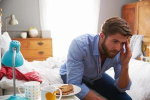 Mann, der an Depressionen leidet, die auf Bettkante sitzen foto