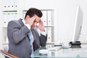 Geschäftsmann, der unter Kopfschmerzen leidet foto