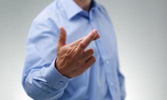 Geschäftsmann mit gekreuzten Fingern foto