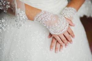 Hochzeitsspitzenhandschuhe an den Händen der Braut, Nahaufnahme foto
