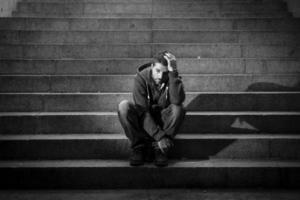 junger Mann leidet an Depressionen, die auf Betontreppen der Grundstraße sitzen