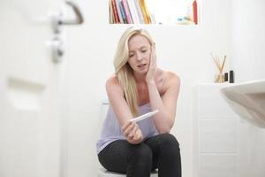 besorgtes junges Mädchen, das im Badezimmer mit Schwangerschaftstest sitzt foto