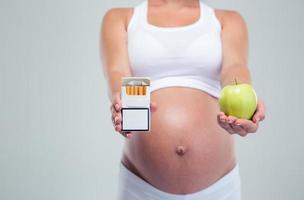 schwangere Frau, die Beetwin Zigaretten und Apfel wählt foto