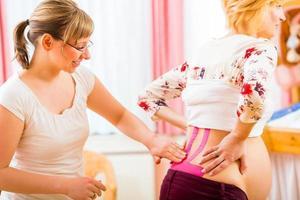 Hebamme, die schwangere Frau mit Kinesio-Band aufklebt foto
