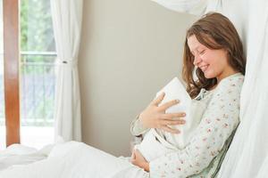 Frau sitzt mit ihrem neugeborenen Kind auf dem Bett