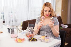 schwangere junge Frau, die Süßigkeiten isst foto