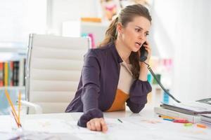 besorgter Modedesigner, der Telefon im Büro spricht foto