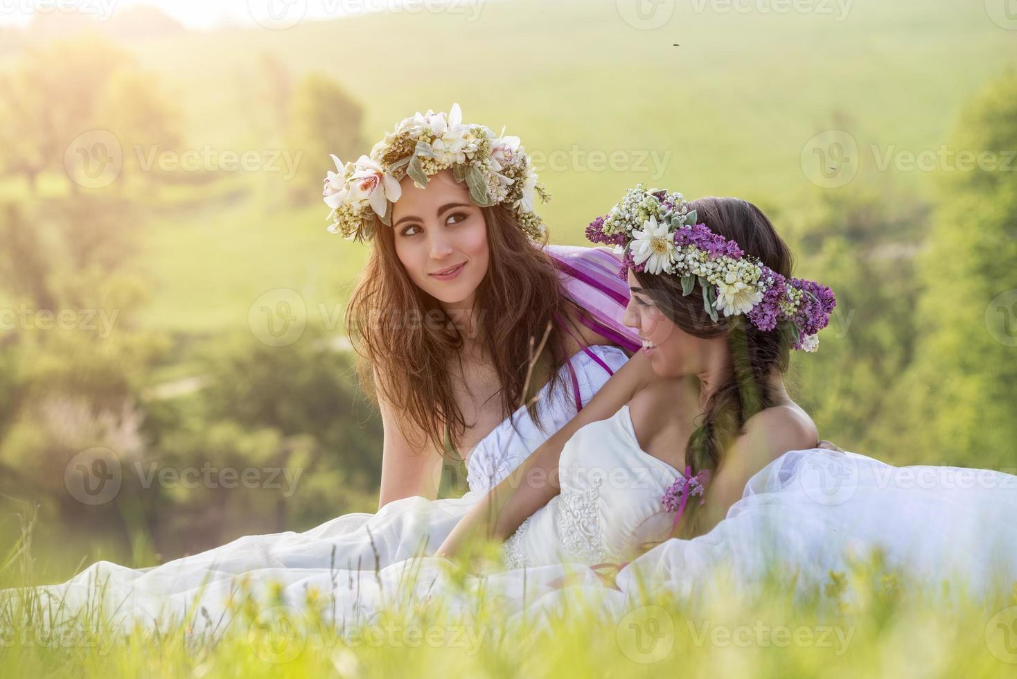 2 vackra brud utomhus, sitter på gräset foto