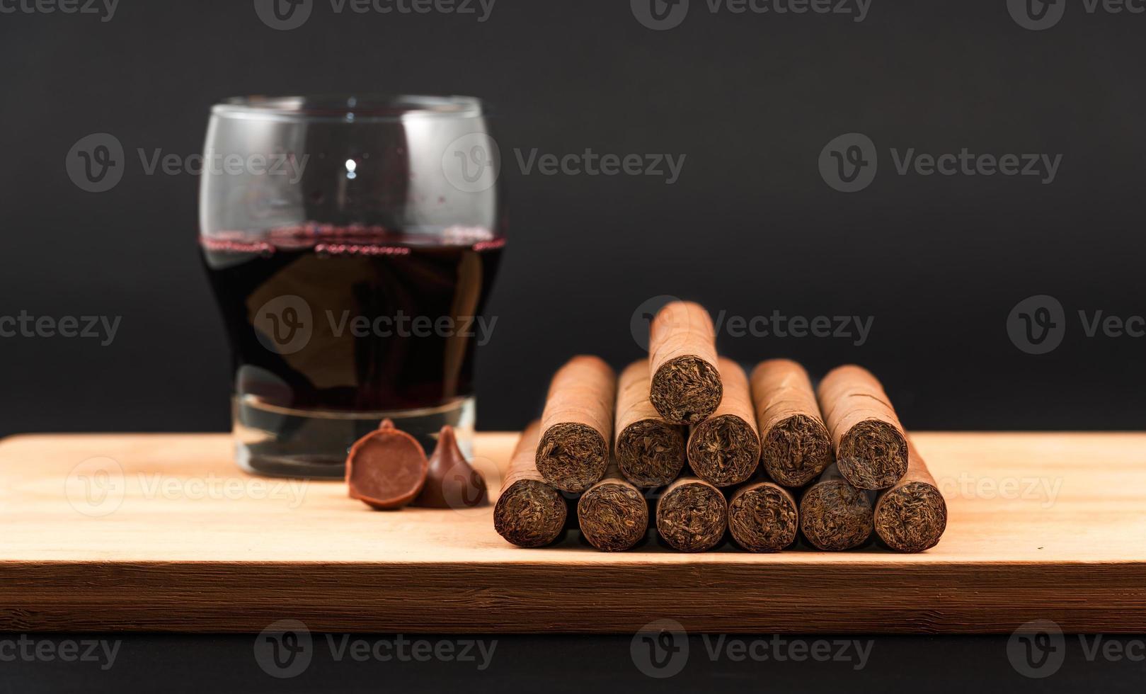 världsberömda handrullade kubanska cigarrer med rött vin foto