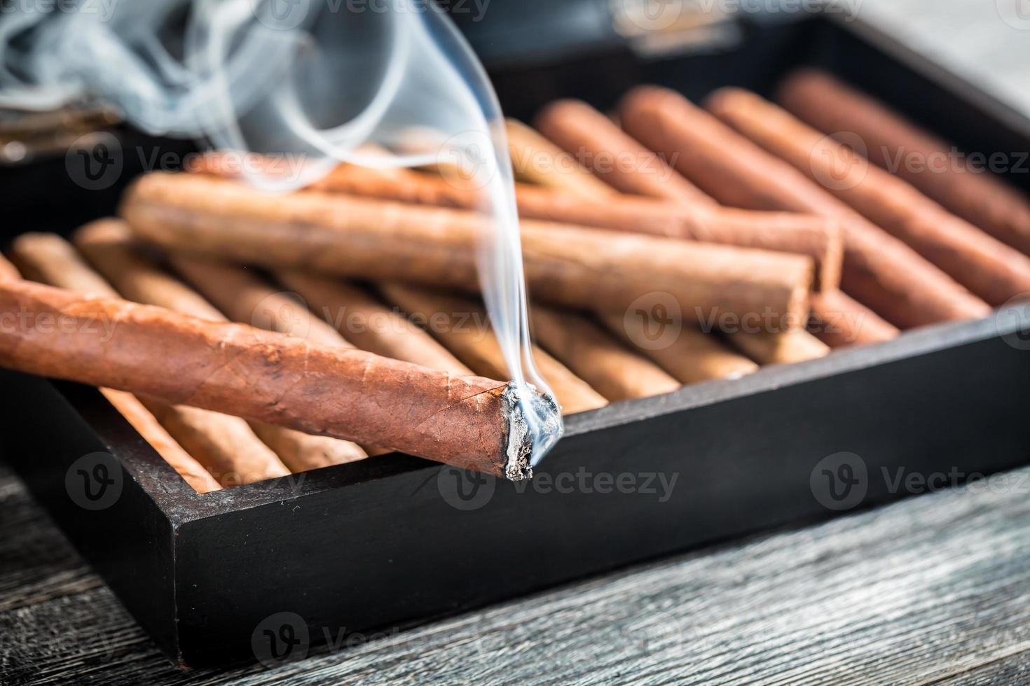 närbild av brinnande cigarr på trähumidor foto