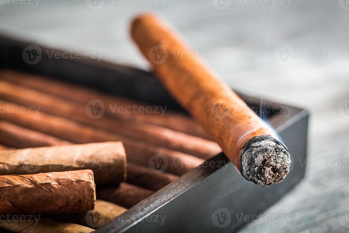 brinnande cigarr med rök på trähumidor foto