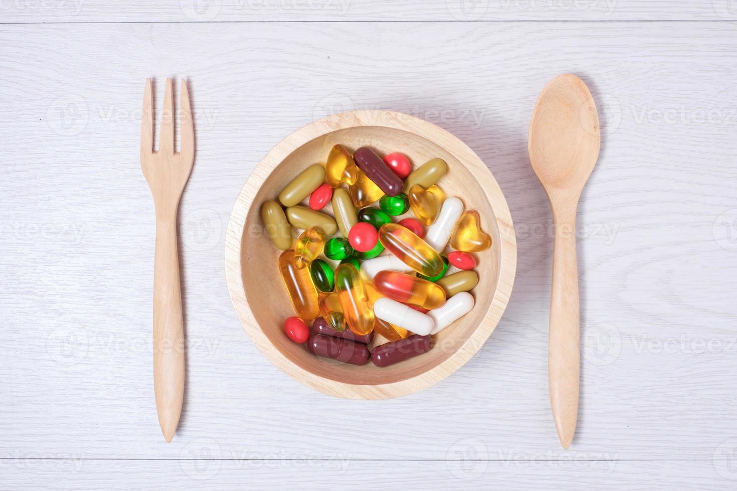 medicin och vitamin på träskål foto