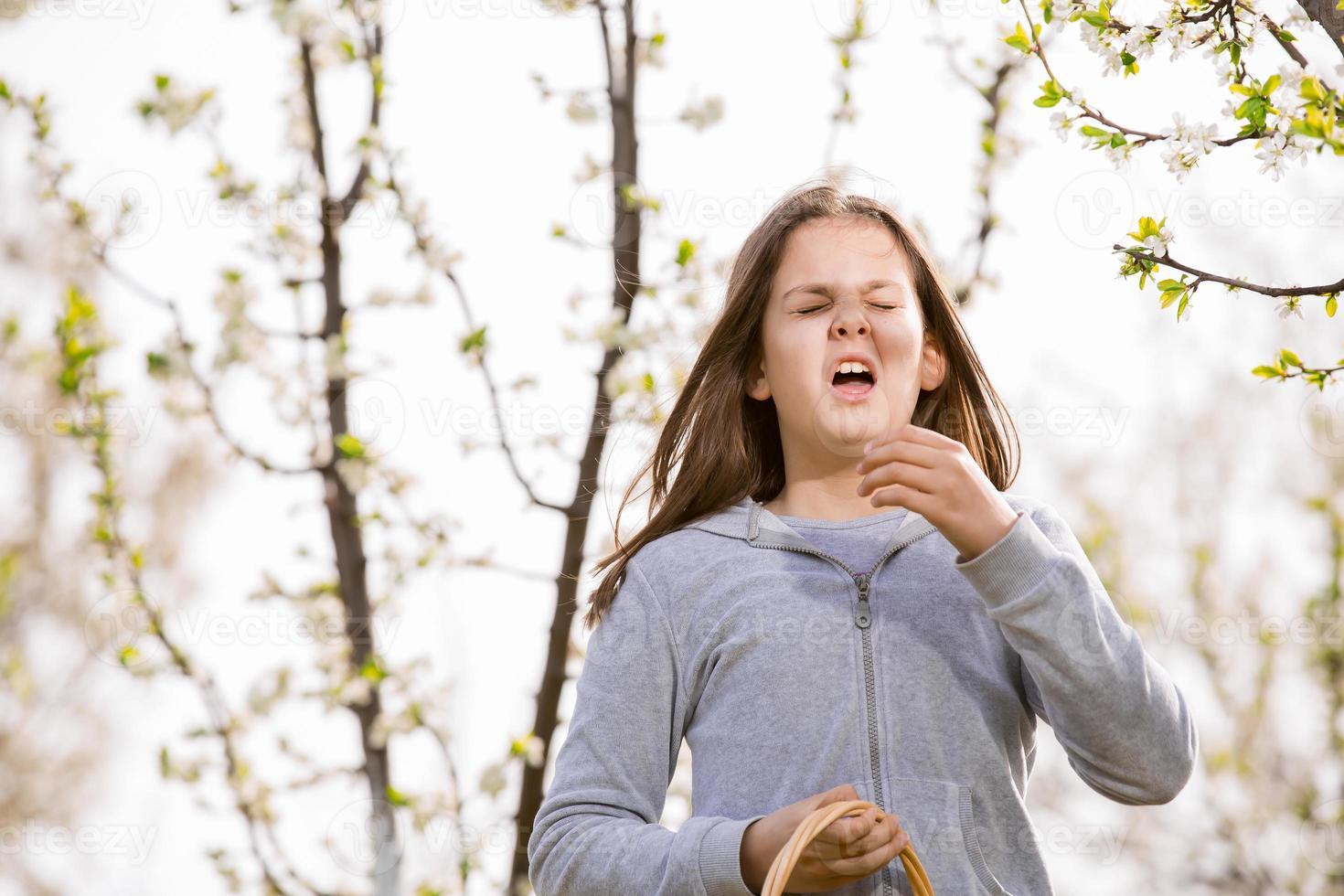 flicka som har allergi utomhus. flickan nysar foto