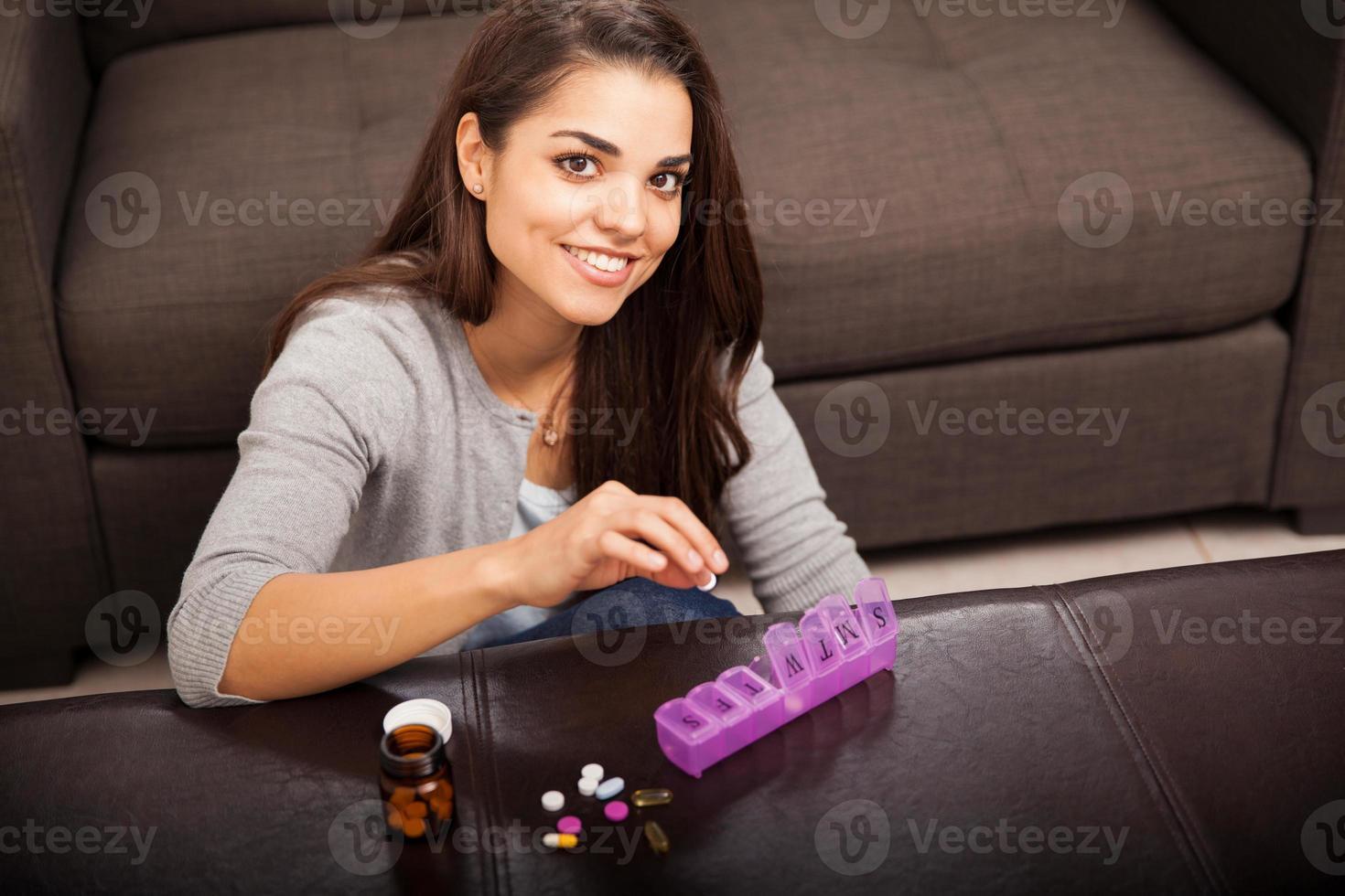söt tjej som organiserar piller foto