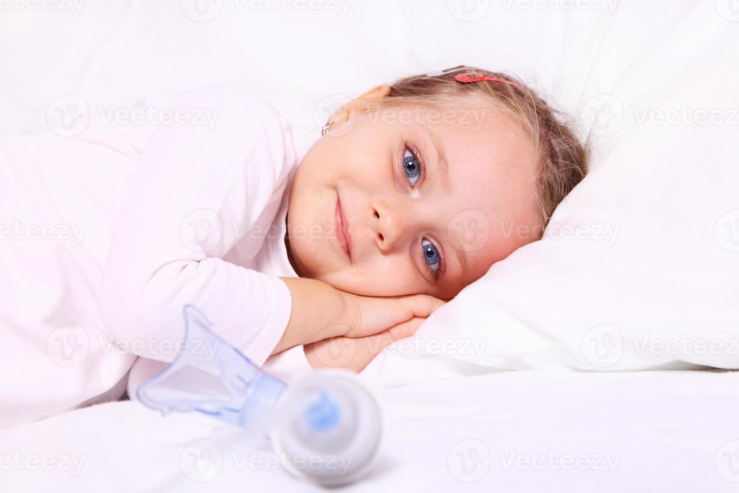 liten flicka efter aerosolbehandling foto