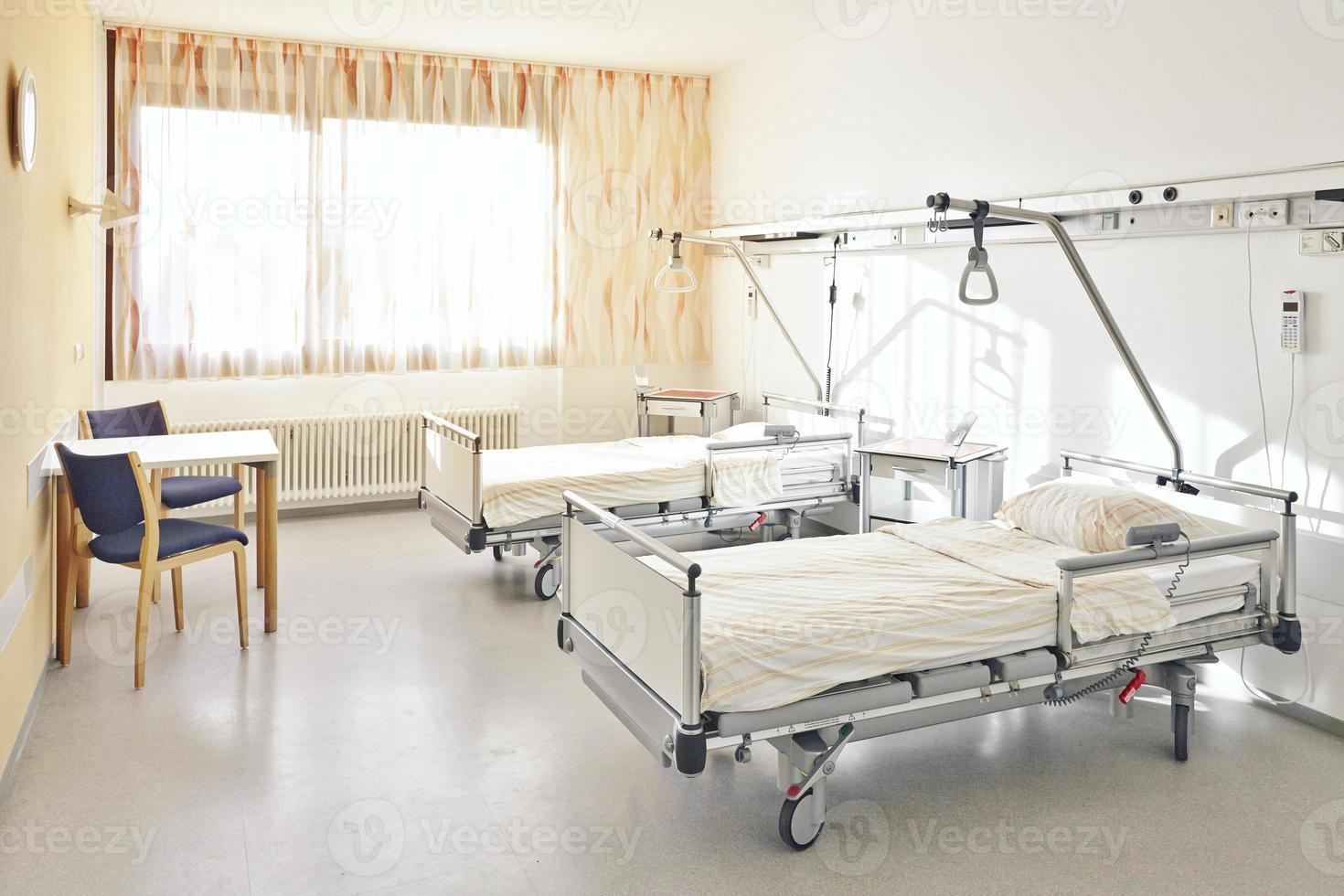 sjukhusrum med två sängar och ett bord med två stolar foto
