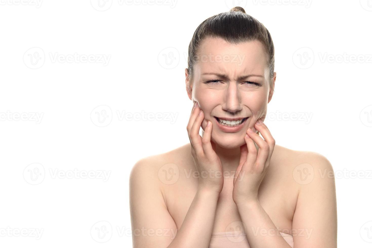 gråtande ung kvinna som lider av tandvärk foto
