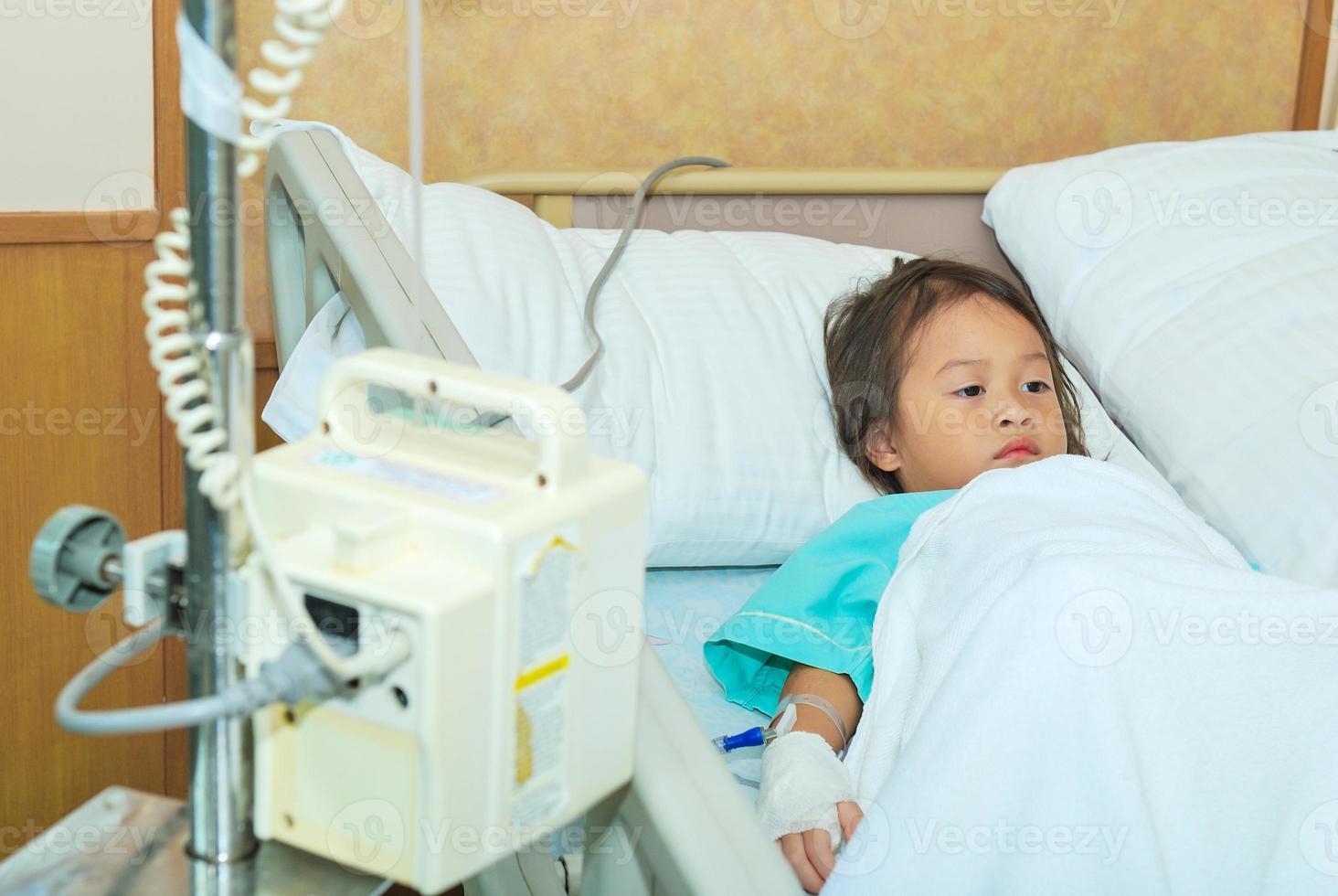 sjuk liten flicka i sjukhussäng foto