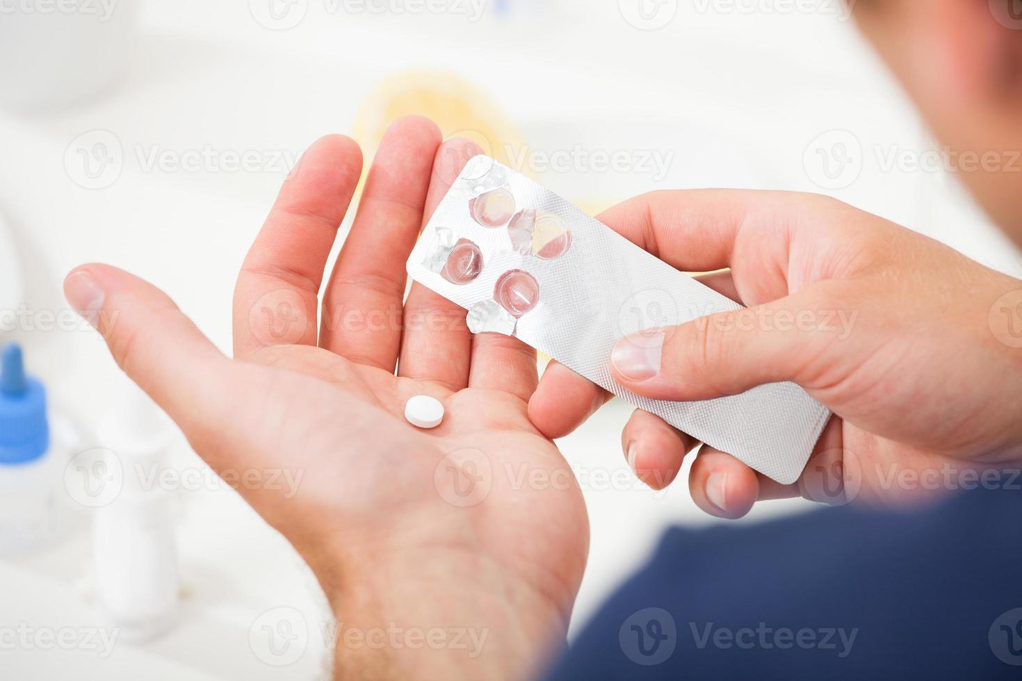man tar ut piller från blisterförpackningen foto