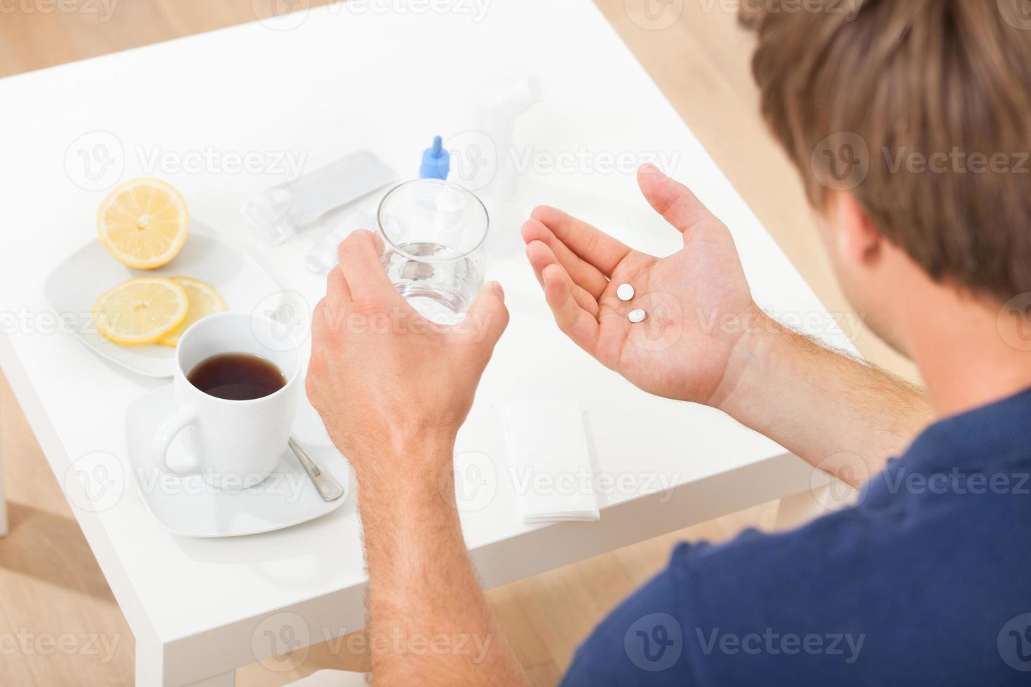 händer som håller piller och vatten foto