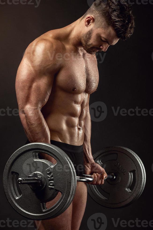 muskulös kroppsbyggare som gör övningar med stor hantel foto