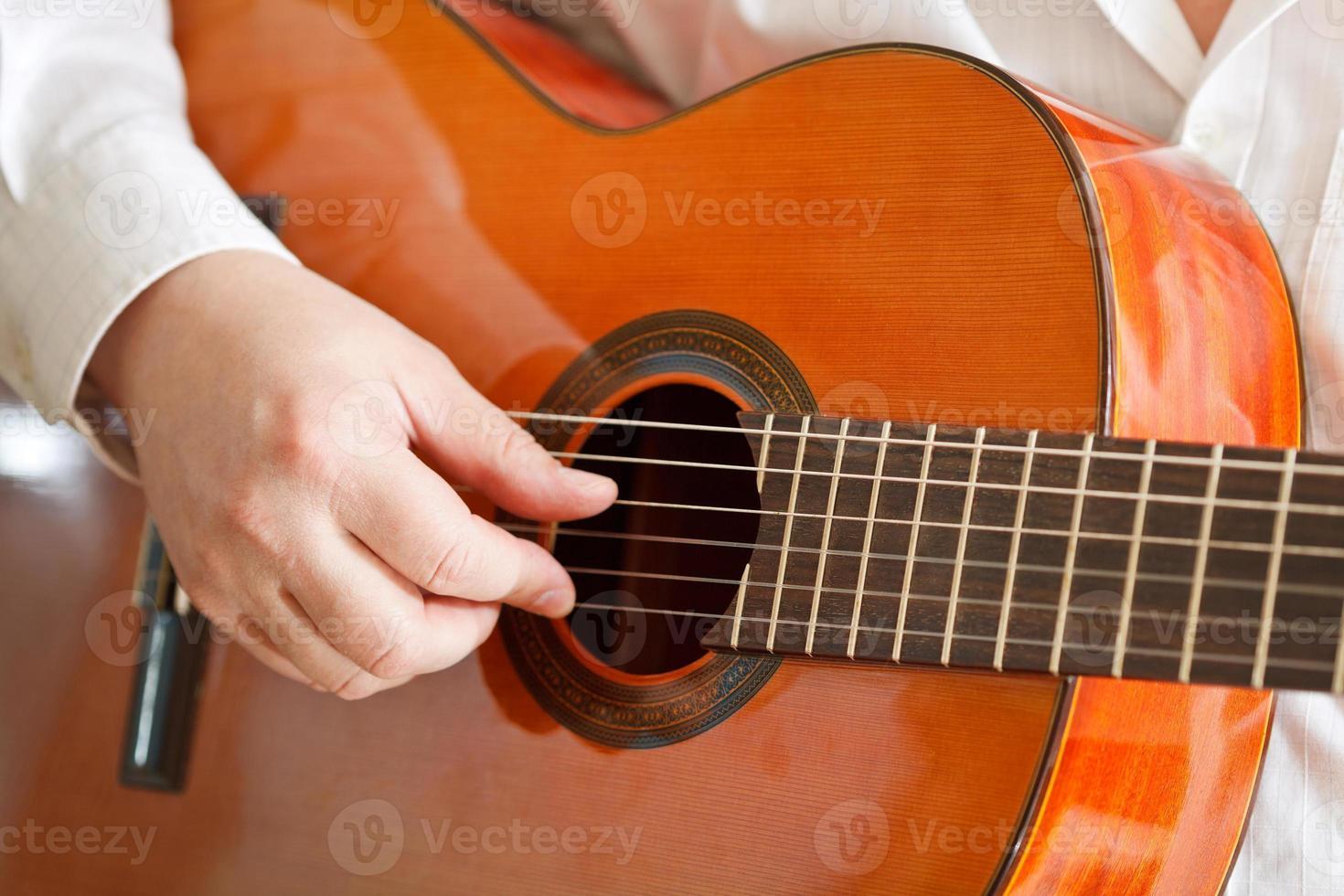 man spelar klassisk akustisk gitarr foto
