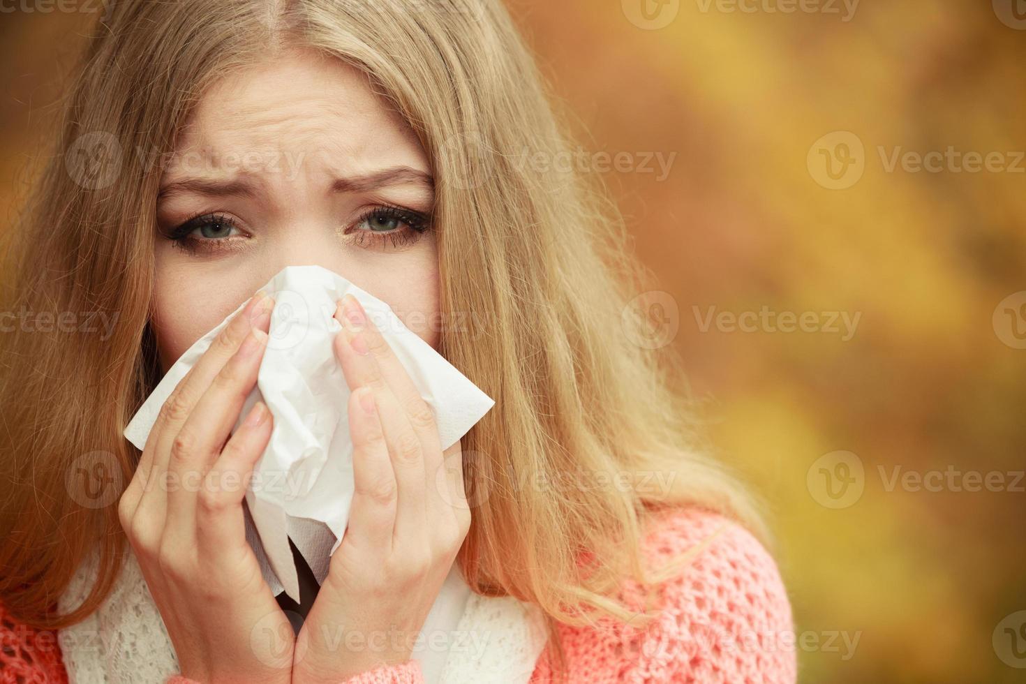 sjuk sjuk kvinna i höst park som nysar i vävnad. foto