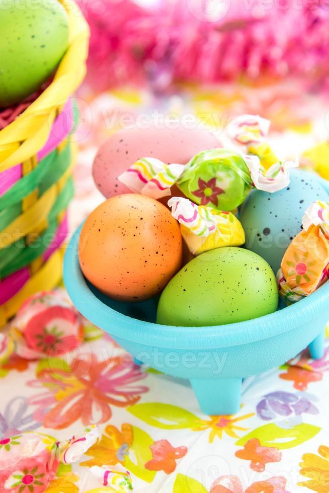 färgade påskägg och godis i blå skål foto
