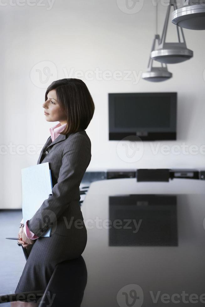 affärskvinna lutad mot konferensbord foto