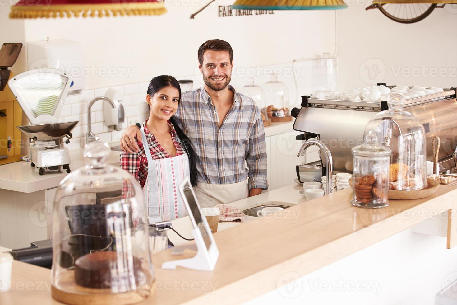 glada unga caféarbetare som ler mot kameran foto
