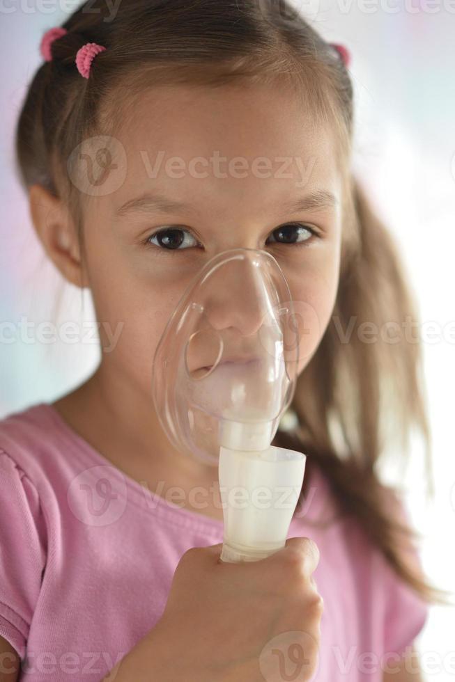 härlig liten flicka med inhalator foto