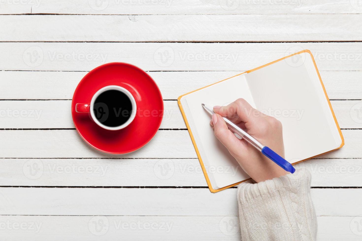 kvinnlig hand som skriver något i anteckningsboken nära kopp kaffe. foto
