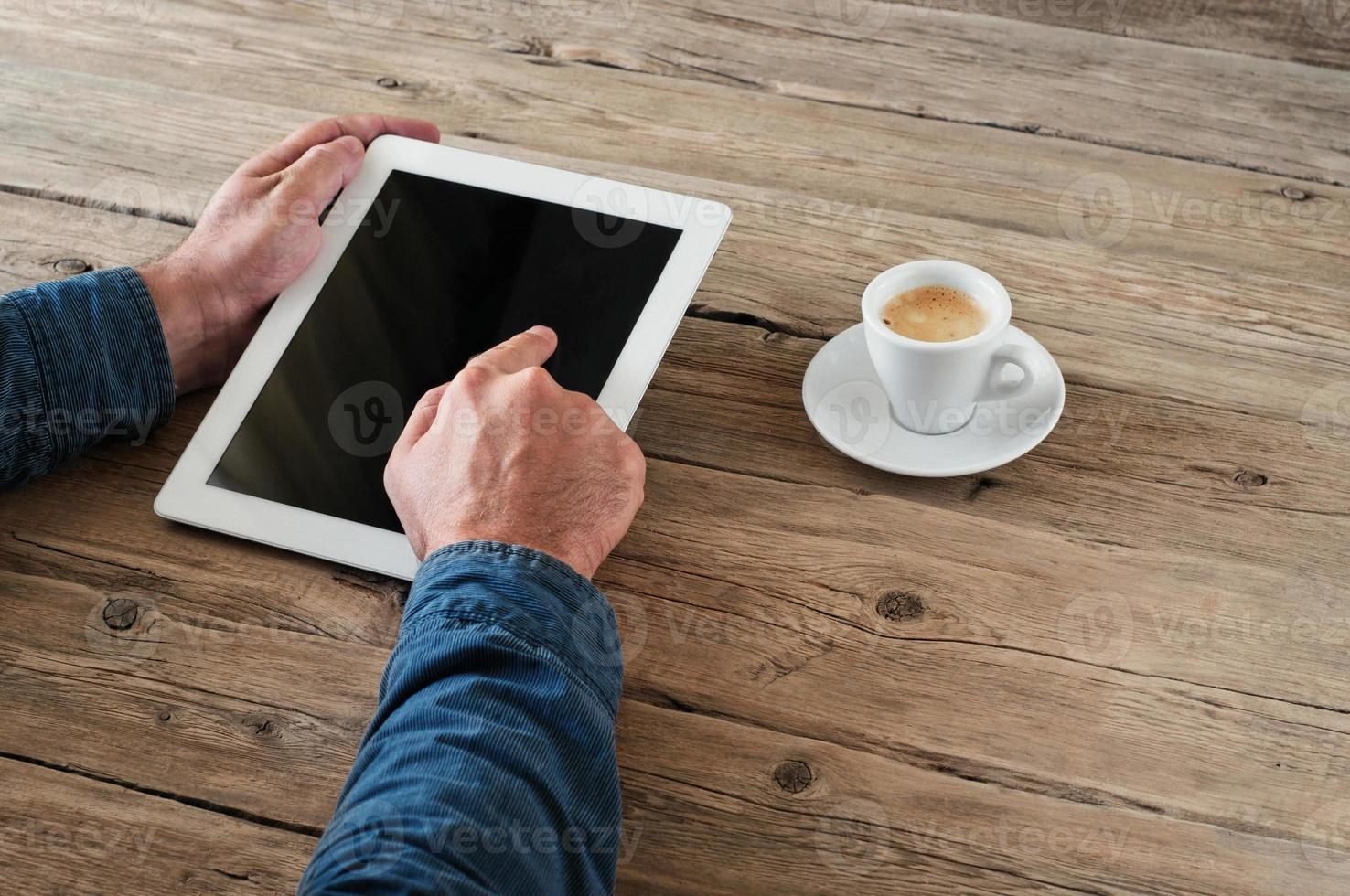 män trycker på den tomma skärmen tablet PC för trä kontor foto