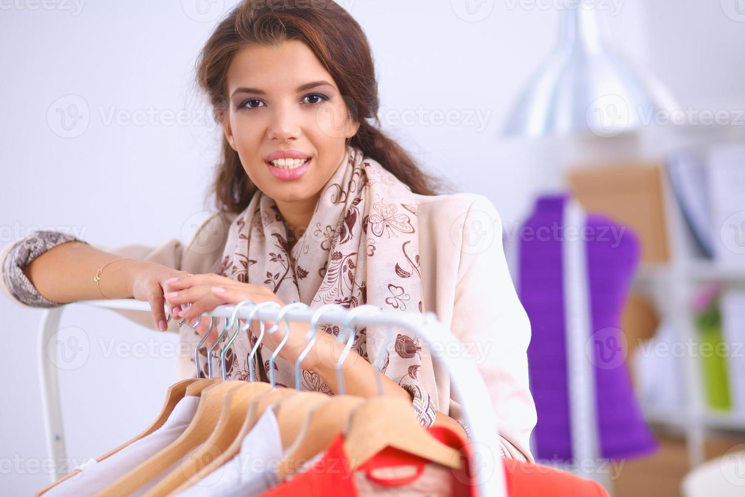 vacker ung stylist nära rack med hängare foto