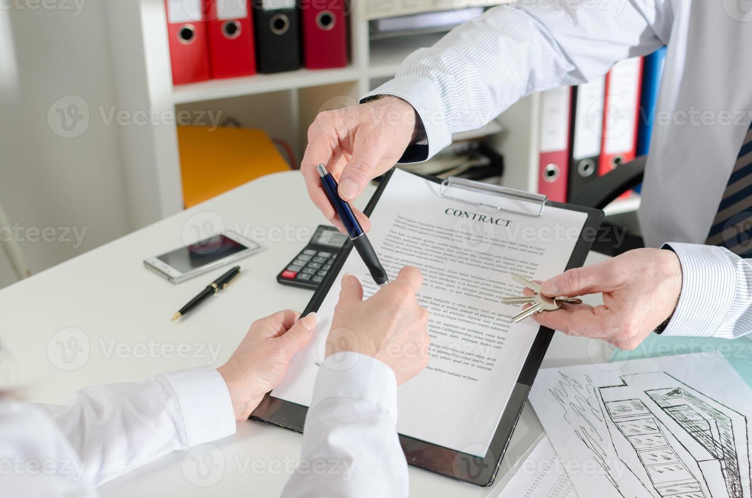 fastighetsmäklare som ger en penna till sin klient för att underteckna kontrakt foto