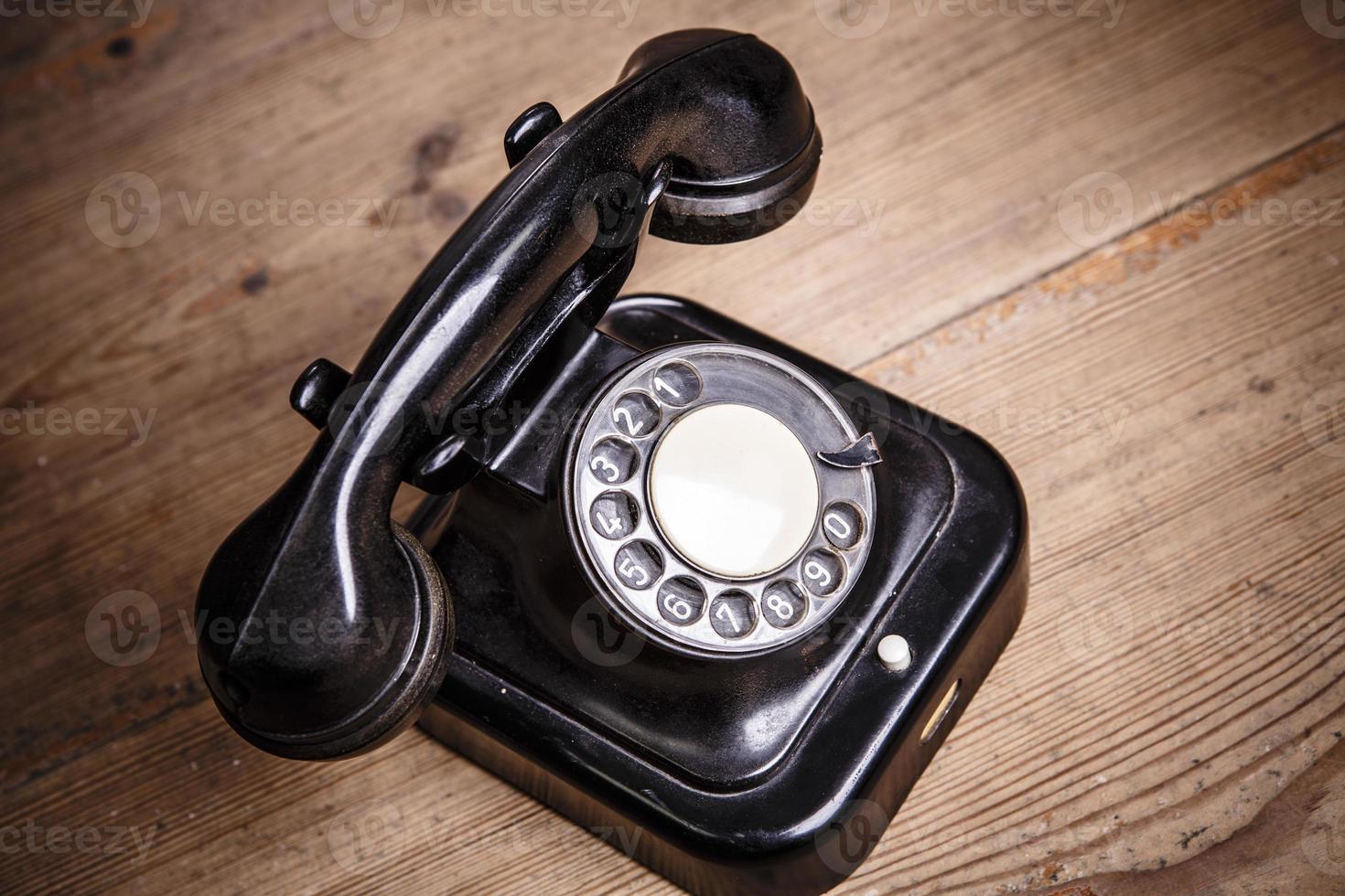 gammal svart telefon med damm och repor på trägolvet foto